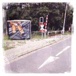 Straße mit Bahnübergang. Ein Pfeil auf Asphalt. Neben der stehenden Schranke ist ein Technikkasten, der mit Graffiti bemalt ist.