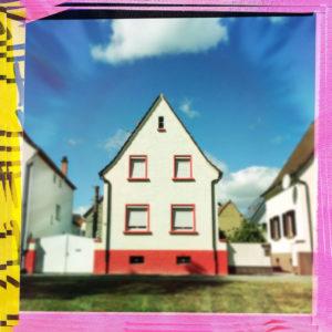 Kleines Haus frontal gesehen mit knallrotem Sockel. Das Bild hat einen bunten rosa-gelben Rahmen. Je zwei nebeneinanderliegende Fenster in den beiden Stockwerken und eine kleine Luke mittig im Giebel. Blauer Himmel mit fetter weißer Wolke.