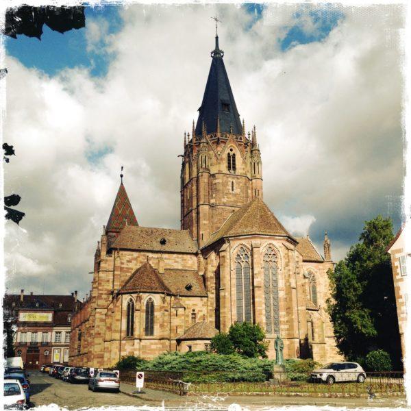 Große Kirche mit spitzem Turm und mehreren im Kreuz verlaufenden Schiffen und stark bewölktem Himmel.