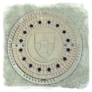 Ein Kanaldeckel Mit dem Wappen und Schriftzug Stadt Westerburg. Grau in grau auf grobem Asphalt.