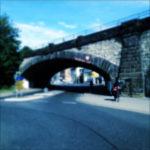 Am Rechten Auflager einer schwer wiegenden Segementbogen-Eisenbahnbrücke steht ein Fahrrad mit Reisepacktaschen. Innerorts offenbar nahe einem Kreisverkehr aufgenommen unter hellblauem Himmel.