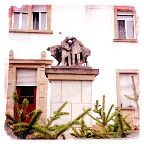 Ein bäuerliches Denkmal auf einem dicken Sockel in einem Vorgarten eines vorstädtischen Wohnhauses zeigt einen Mann, der einen Bullen führt.