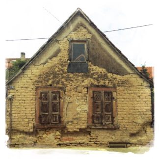 Gibel eines alten Hauses mit einem großen Fenster mittig über zwei großen Fenstern. Der lehmfarbene Verputz blättert ab.