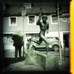 Schwarzweißbild eines Bronzedenkmals, rennender Junge vor innerstädtischer Fußgängerampel. Mit dem Rücken zu Jüngling und Betrachterin steht ein wuchtiger Mann mit Anzug an der Ampel. Ins Schwarzweiß brennt sich von rechts fehlfarbig ein gelborangener Belichtungsfehlerrand.