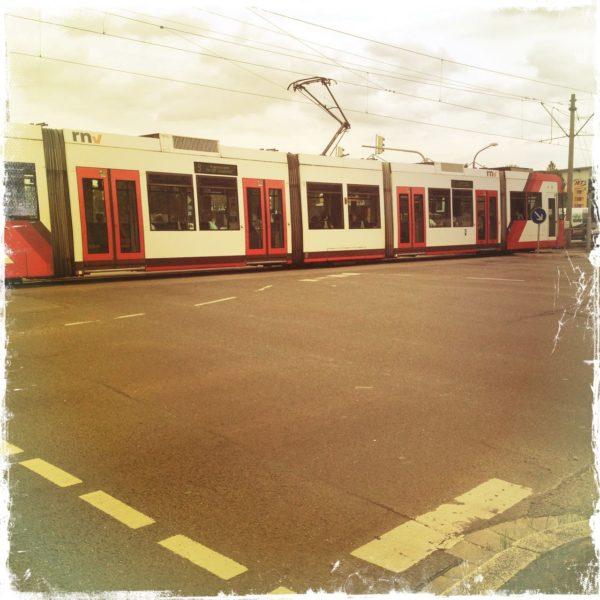 Im oberen Drittel des quadratischen Bilds durchquert eine rot-weiße Straßenbahn die Szene. Die beiden unteren Drittel zeigen Teer, Straße, Markierungen in einem rötlichen Teint.