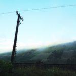 Ein markanter Mast auf einem Bahndamm führt den Betrachter, die Betrachterin ins Bild fern zu Hängen, die von Morgennebel geleitet in den seichtblauen Himmel ragen. Weinbergszeilen geben dem steilen Hang eine schachbrettartige Struktur.