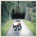 Ein Bahntrassenradweg führt in einen Tunnel, an dessen Scheitel schlingernde Pflanzen wie ein Fransenvorhang herabhängen. Ein bepacktes Reiserad steht aufgebockt mitten auf der schmalen Trasse.