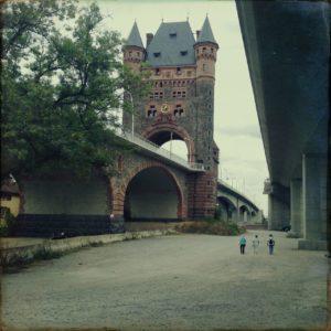 Unter einer neuen Brücke stehend blickt man längs der Brückenverläufe auf den Turm des Brückenkopfs eiiner alten, parallel führenden Brücke. Der Turm hat ein Hausdach mittig und zwei Türmchen rechts und links daneben. drei winzige Fußgängerinnen sind ausmachbar auf der garstig geteerten Fläche zwischen den beiden Brücken.