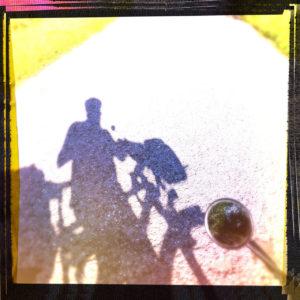 Schatten eines Fahrradfahrers oder einer Fahrradfahrerin mit Helm auf fast bleichem Teer, Fehlbelichtung mit gelblichem Einschlag und scharzem Rand, der an der linken oberen Ecke ins rötliche driftet. Neben dem Schatten ragt von rechts ein kleiner runder Fahrradspiegel ins Bild.