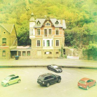 Ein einzelstehendes Haus, etwas von oben von einem Bahndamm betrachtet, mit einem Parkplatz, auf dem schräg drei Autos geparkt sind, Auto, Lücke, Auto, was dem Bild eine eigenwillige Pseudosymmetrie verleiht. Das Bild ist stark fehlfarbig mit gelblichem Stich.