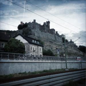 Im blaustichigen Bild thront eine Mittelrheinburg über Dorfhäusern und Bahnlinie, die am unteren Bildrand schräg verläuft und etwa ein sechstel der Bildhöhe einnimmt. Der milchig bewölkte Himmel wirkt düster.