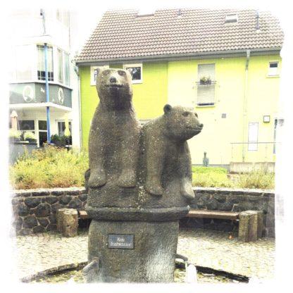 Zwei kleine Bärenfiguren aus Stein in einem leeren, außerbetrieben Springbrunnen.