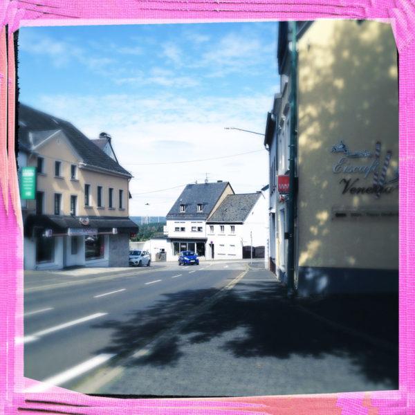 Innenstadtszene mit Straße links im Bild, halb angeschnitten. Rechte Bildseite eine Hausfassade mit Schriftzügen. Das bIld hat einen rosa Rahmen und ist blaugrau getönt. Ein nicht sichtbarer Baum rechts wirft einen großen Schatten auf den Teer.