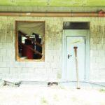 Baustelle mit frischer Fassade unter Vorbau. Oberhalb schattiert. Die Tür ist mit einer schräg stehenden Baustütze versperrt. Im spiegelnden Fenster links daneben stehen Gegenstände.
