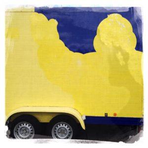 Ein großer PKW-Anhänger mit Doppelachse von der Seite betrachtet. Auf der Bordwand die gelbe, verwitterte Silhouette eines offenbaren Michelinmanns, der die Hand schemenhaft ins dunkle Blau des Hintergrunds reckt. Nur ansatzweise sind die bereiften Räder der Doppelachse am unteren Bildrand erkennbar.