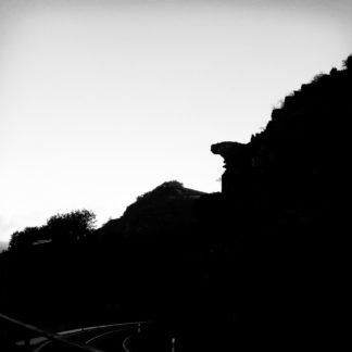 Zersiedelte Diagonale Linie von links unten nach rechts oben zeigt offenbar eine Bergsilhouette, aus der ein Felsvorsprung herausragt. Rechts unten fast schwarz, links oben fast weißes Bild.