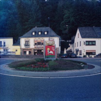 Kreisverkehr zentral im Bild vor Walm bedachtem Haus. Auf dem Kreisel ein rotes Stadtwappen mit weißem Motiv