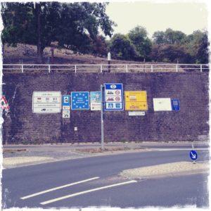 Viele rechteckige Hinweisschilder auf Autobahnen und Bundesstraßen stehen in Reih und Glied vor einer hohen Mauer, über der sich eine Art Streuobstwiese befindet.
