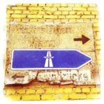Auf gelber Backsteinwand ist auf einem verwitterten Holzschild ein Autobahn-Hinweisschild angebracht.
