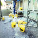 Vor der eingerüsteten Fassade eines städtischen Hauses stehen gelbe Malereimer auf dem Pflaster. Offenbar befinden wir uns in einer Fußgängerzone.