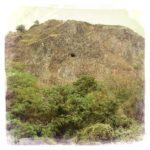 Winziger schwarzer Punkt in wuchtigem Schieferfelsen über wildem Baumbewuchs. Der Punkt ist der Eingang einer Höhle mitten in der Steilwand.