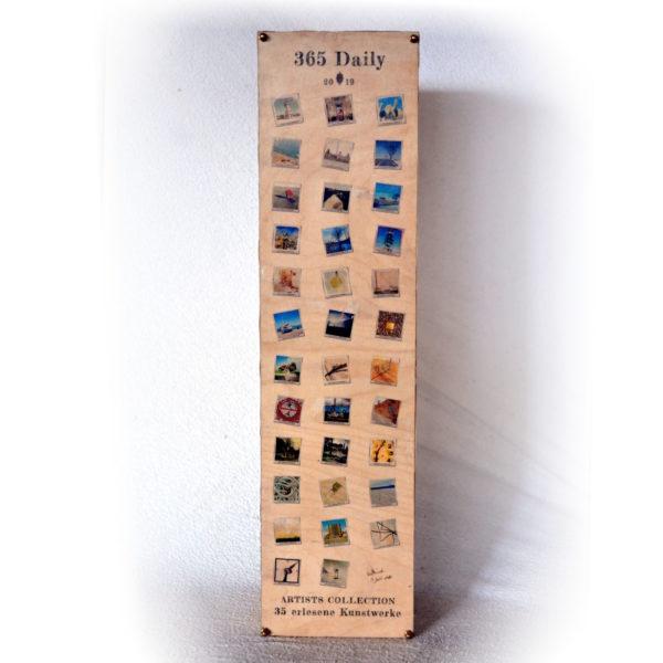 Eine Holzbox mit bedrucktem Deckel, der mit vier Messingschrauben befestigt ist. Ursprünglich ein Ikea CD-Ständer. Aufgedruckt sind 35 kleine quadratische bunte Bildchen unter der Schrift 365 Daily 2019. Die Bildchen im Polaroidstil sind zufällig verwinkelt in drei Spalten angeordnet. Ganz unten steht geschrieben Artists Collection. 35 erlesene Kunstwerke.