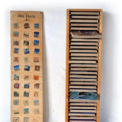 Offene Holzbox, Deckel steht links daneben. Aus den Fächern mit Kunstwerken ragen zwei etwa heraus wie Schubladen. Box Artists Collection.