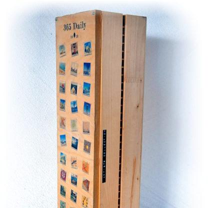 Hölzerne Box, die einst für CDs gedacht war von der Seite, aufrecht stehend. Man sieht einen Teil des bedruckten Deckels, sowie imt einem Dymo-Klebeschriftband seitlich schwarz mit weißer Prägung den Schriftzug Artists Collection.