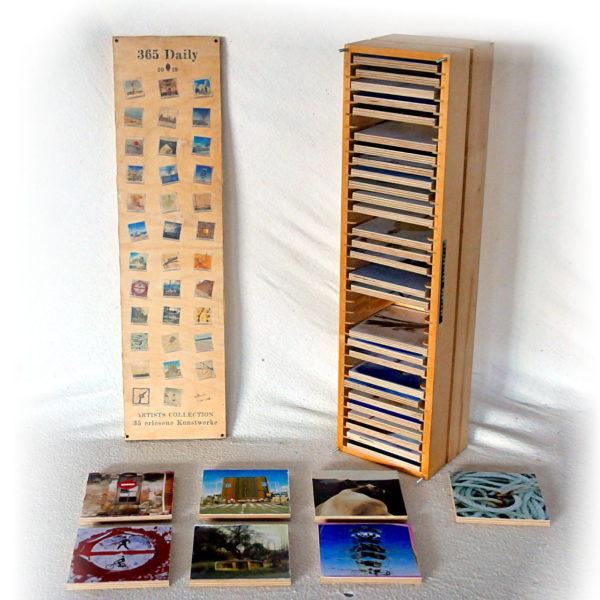 Offene Kunstbox aus Holz, länglich, aufrechtstehend wie CD-Ständer von Ikea. Links der bedruckte Deckel, rechts die Box, aus der einige bunte quadratische Kunstwerke entnommen sind, die vor Deckel und Box auf dem Tisch liegen.
