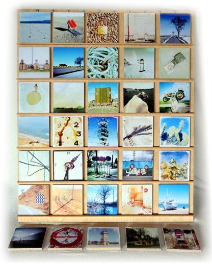 35 kleine quadratische Kunstwerke auf einem hölzernen Display in Reih und Glied arrangiert. Eine Kuh, eine Uhr, ein Baum vor Tümpel, Palme, Traktor auf einem Pfosten, der wie ein Denkmal aussieht Kaktus und viele viele mehr.
