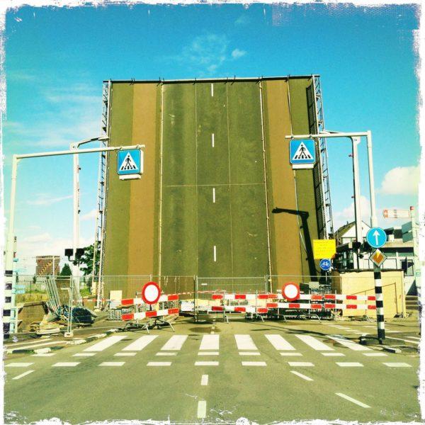 Senkrecht gestellte Zugbrücke ragt in den Himmel. Davor Zebrastreifen und Schilder und eine rotweiße Absperrung. Mittig auf der senkrechten Fläche die gestrichelte Straßenmarkierung und deutliche Fahrspuren auf Teer.