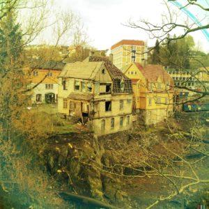 Zwischen Zweigen hindurch schaut man auf ein verwinkeltes altes Haus, das schon ziemlich zerfallen ist und dessen Fenster und Türen fehlen.