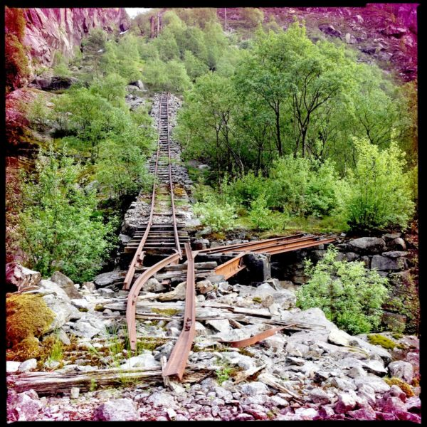 Zerworfene alte Bahnschienen führen einen steilen Hang hinauf auf eine Felswand zu. Umrankt werden sie von jungem Grün. Die Schiene hat eine Weiche nach rechts und ist im Vordergrund wie abgerissen auf Felsbrocken züngelnd.