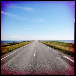 Schnurgerade Straße durch flaches Land führt auf den Horizont zu. Der Himmel ist blau, die Straße leer.