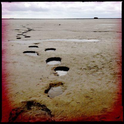 Ovale Fußstapfen führen ins Wattenmeer. Am Horizont ein kleiner dunkler Punkt, vielleicht ein fernes Schiff.