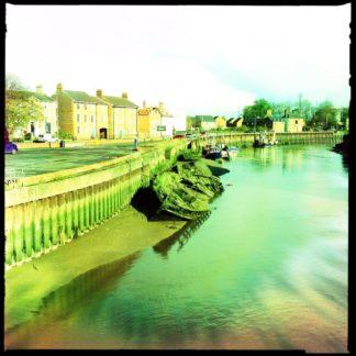 Blick auf einen Meernahen Flusshafen bei Ebe. Grünstichig fehlfarbig liegt ein alter Holzkahn auf Schlick an der Hafenmauer vertäut. Im Hintergrund englische Stadtszene.