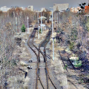 Blick auf eine Bahnanlage. Leicht solarisiertes Farbfoto. Eingebettet zwischen Bäumen liegen die Weichen, steht ein Bahngebäude. Am Horizon Hochwohngebäude