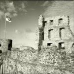 Schwarzweißbild einer Burgmauer. Auf dem runden Turm links im Bild weht eine Fahne