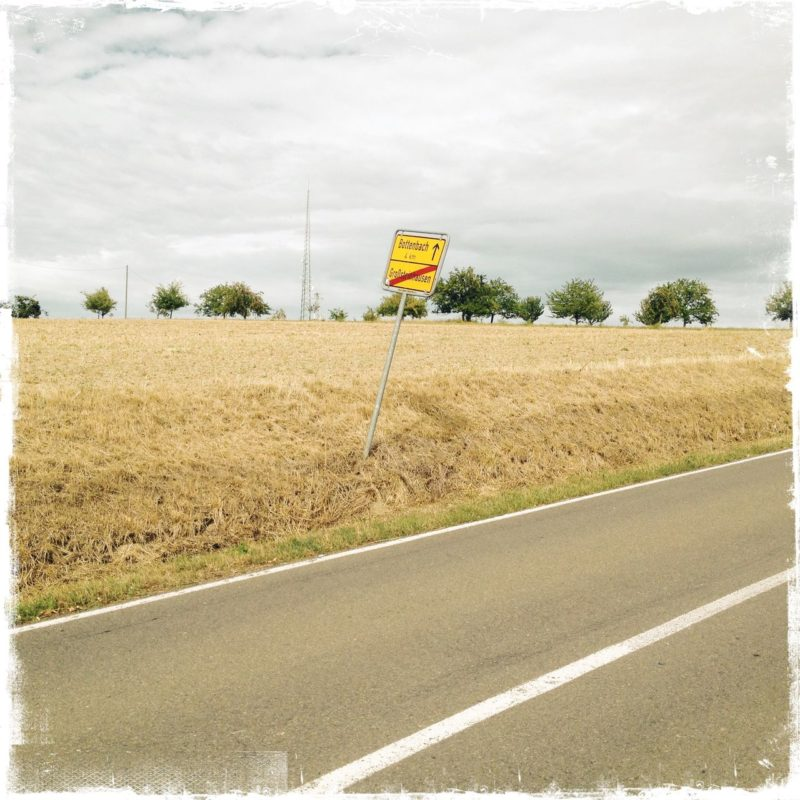 Schräg nimmt das graue Band, das niemals endet, eine Landstraße den unteren Bildteil ein. Durchgezogene weiße Mittellinie. Ein Ortsausgangsschild eröffnet Weite, die sich in einem gelben abgeertnteten Kornfeld verliert, garniert von einem Streifen Bäume und milchigem Sommerhimmel.