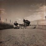 Links neben dem bepackten Reiserad, das aufgeständert mitten auf dem geteerten Weg steht, sitzt im Schneideristz der Radler. Underfootaufnahme, schwarzweiß, bodennah.