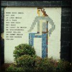 Mosaik auf Fliesen an Hauswand zeigt einen Menschen neben einer mehrzeiligen Inschrift