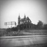 Scharzweiß-Bild eines Kirchbaus in einem flachen Rebenland neben einer Bundesstraße. Großes Domänenhinweisschild zwischen den Reben.