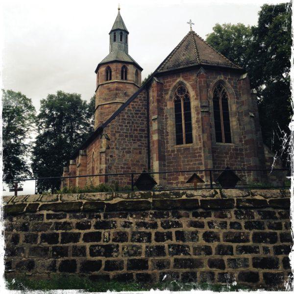 Im unteren Drittel des quadratischen Motivs liegt braun die Sandsteinmauer eines Kirchhofs, über dem sich eine Sandsteinkirche mit achteckigem Turm erhebt.