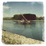 An einem großen Fluß blickt man über die schräg unten links durchs Bild laufende Uferbefestigung aus hellgrauen Seinen auf den blaugrau schimmernden Fluss und darüber hinaus auf die von hohen dunklen Bäumen bewachsene andere Flusseite. Im Wasser schwimmt ein Baggerschiff mit schräg stehendem Kran.
