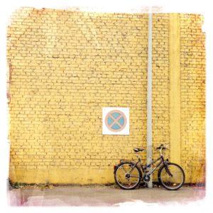 Beige Backsteinwand mit Regenfallrohr und Parverbotsschild, an der, etwas exzentrisch rechts ein altes Damenfahrrad lehnt.