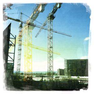 Mehrfach überblendendes Bild zweir Baukrane vor noch fast leerem zu bebauendem Gelände.