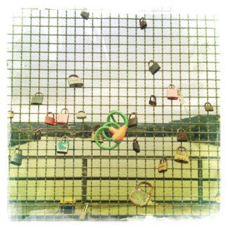 Am engmaschigen Gitter einer Brückengeländersicherung hängen einige Vorhängeschlösser, siese typischen, die die Liebenden aufhängen und den Schlüssel anschließend im Fluss versenken.