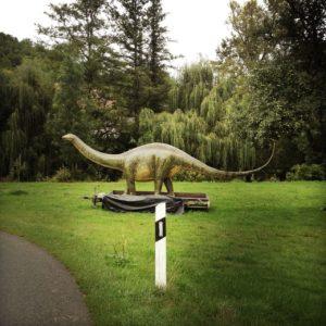 Dinosauriermodell auf Anhänger in grüner wiese, Kopf nach links, Schwanz nach rechts