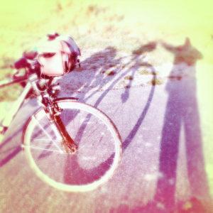 Lenker und Vorderrad eines Reiserads, neben dem sich der Fotograf als rötlich fehlfarbener Schatten abbildet.