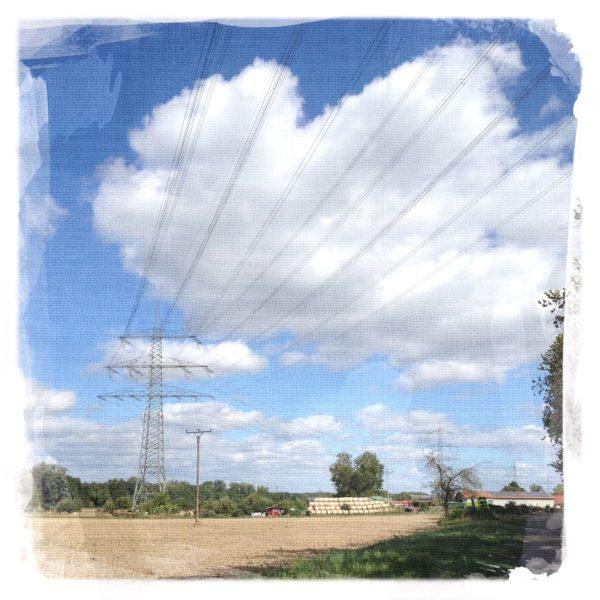 Landschaftsbild mit hellblauem, bewölktem Himmel und dominanter Stromleitungsführung wie Gespinst.